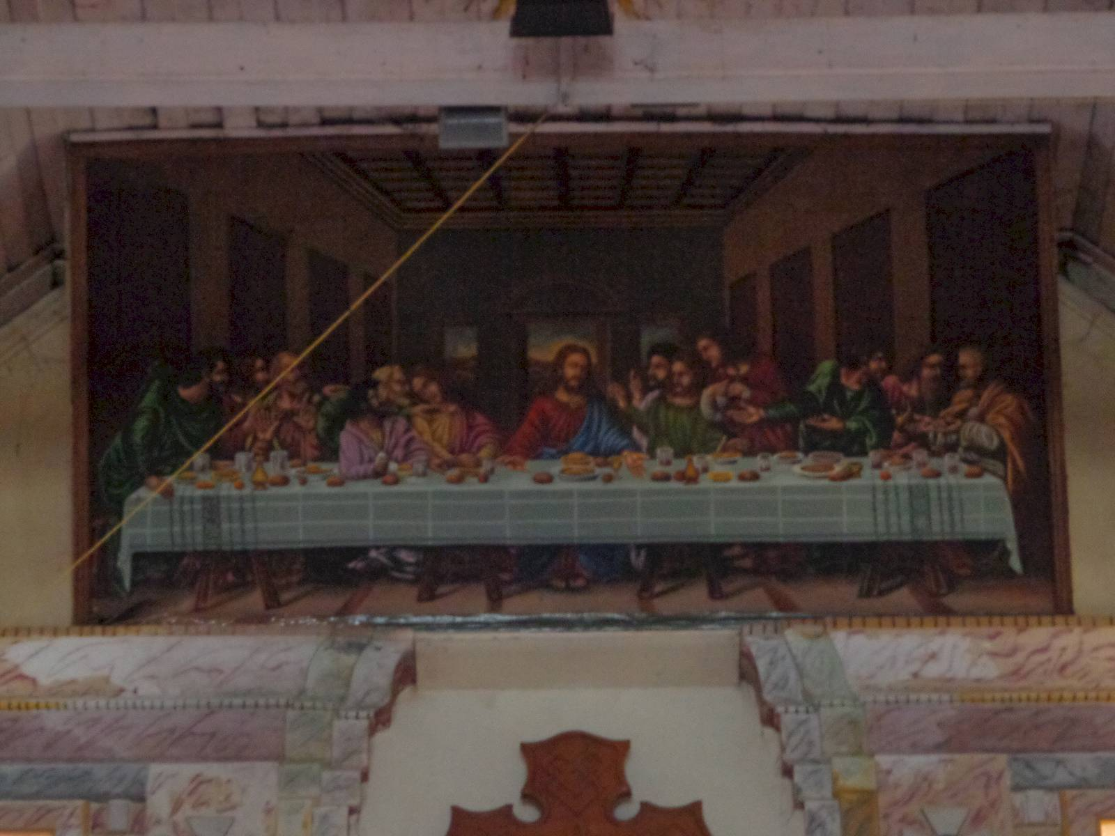A depiction of The Last Supper was painted high up  on the wall behind the alter.