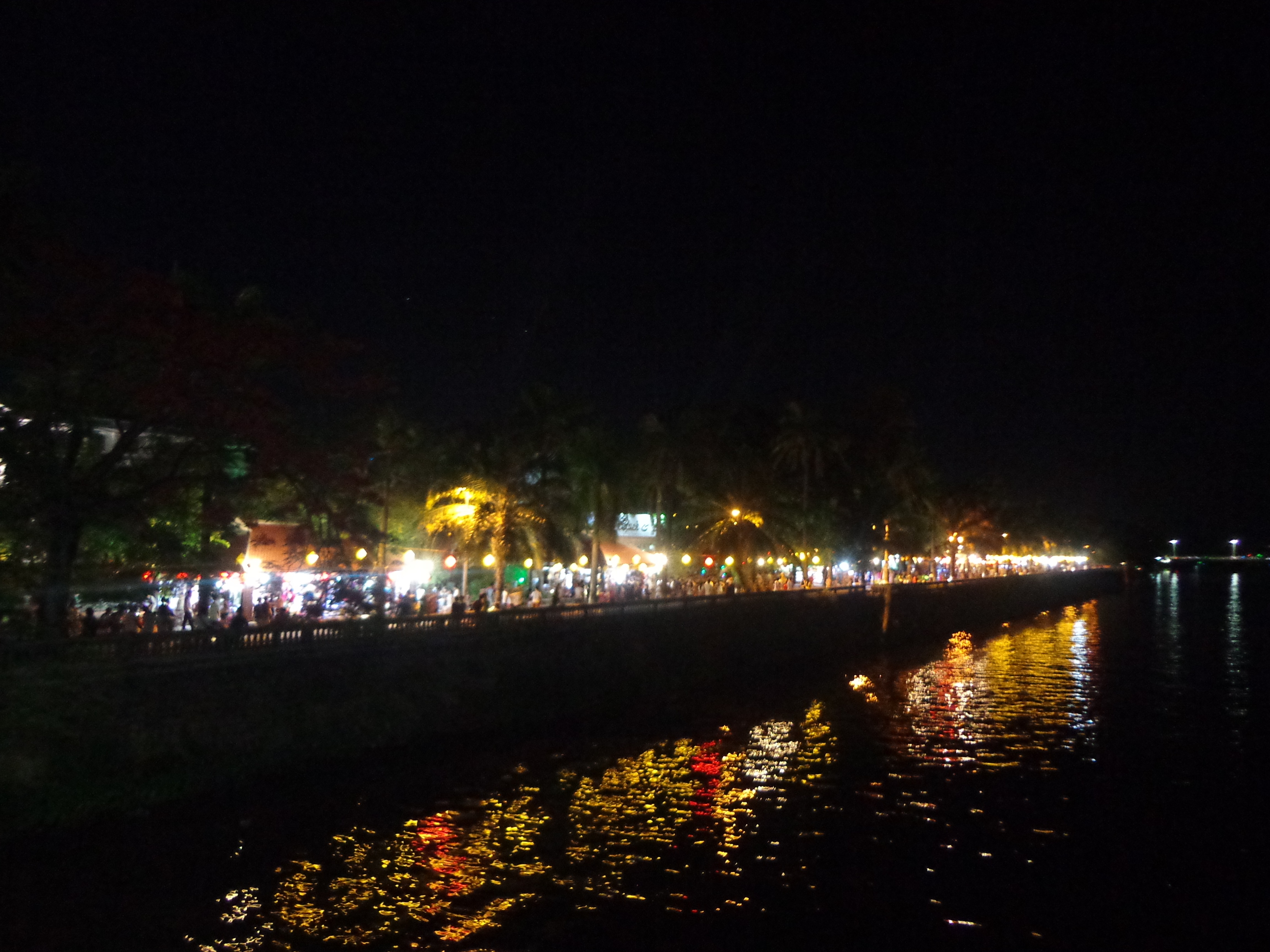 Perfume river at night illuminated by commercial establishments across the river.