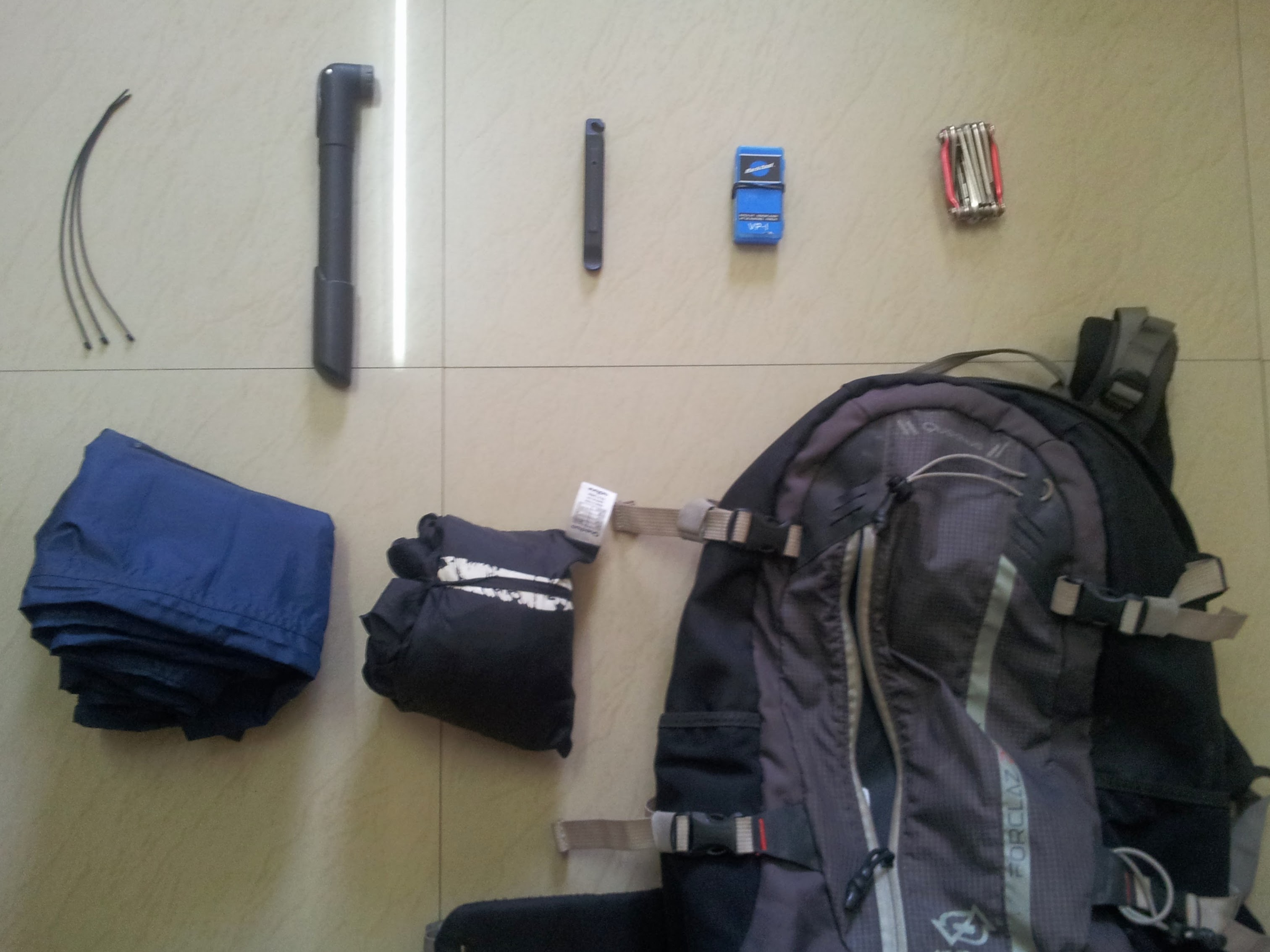Top L-R: Cable ties, Hand pump, pair of tyre levers, Patch kit, Multitool. Bottom L-R: Rainproof lower trousers, Rainjacket, Backpack. I do not carry a spare tyre as I have a shop right beside my office in case I need to get one. The commute distance is less, too.