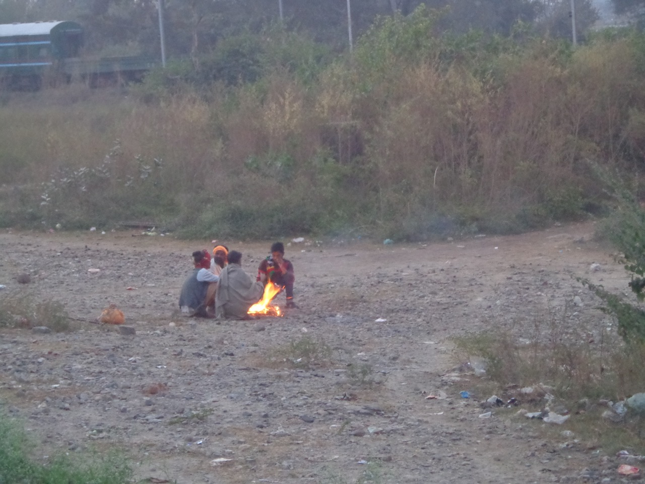 Guys warming themselves up near a bonfire just off the tracks at Pathankot Cantt. station.
