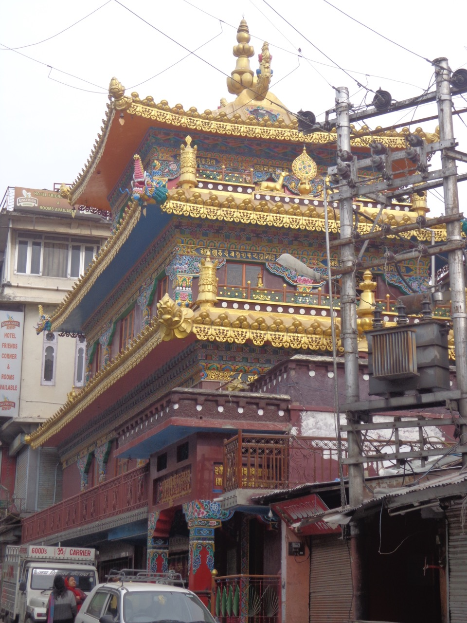 Kalachakra Temple sandwiched between modern eateries, shops and electrical transformer.