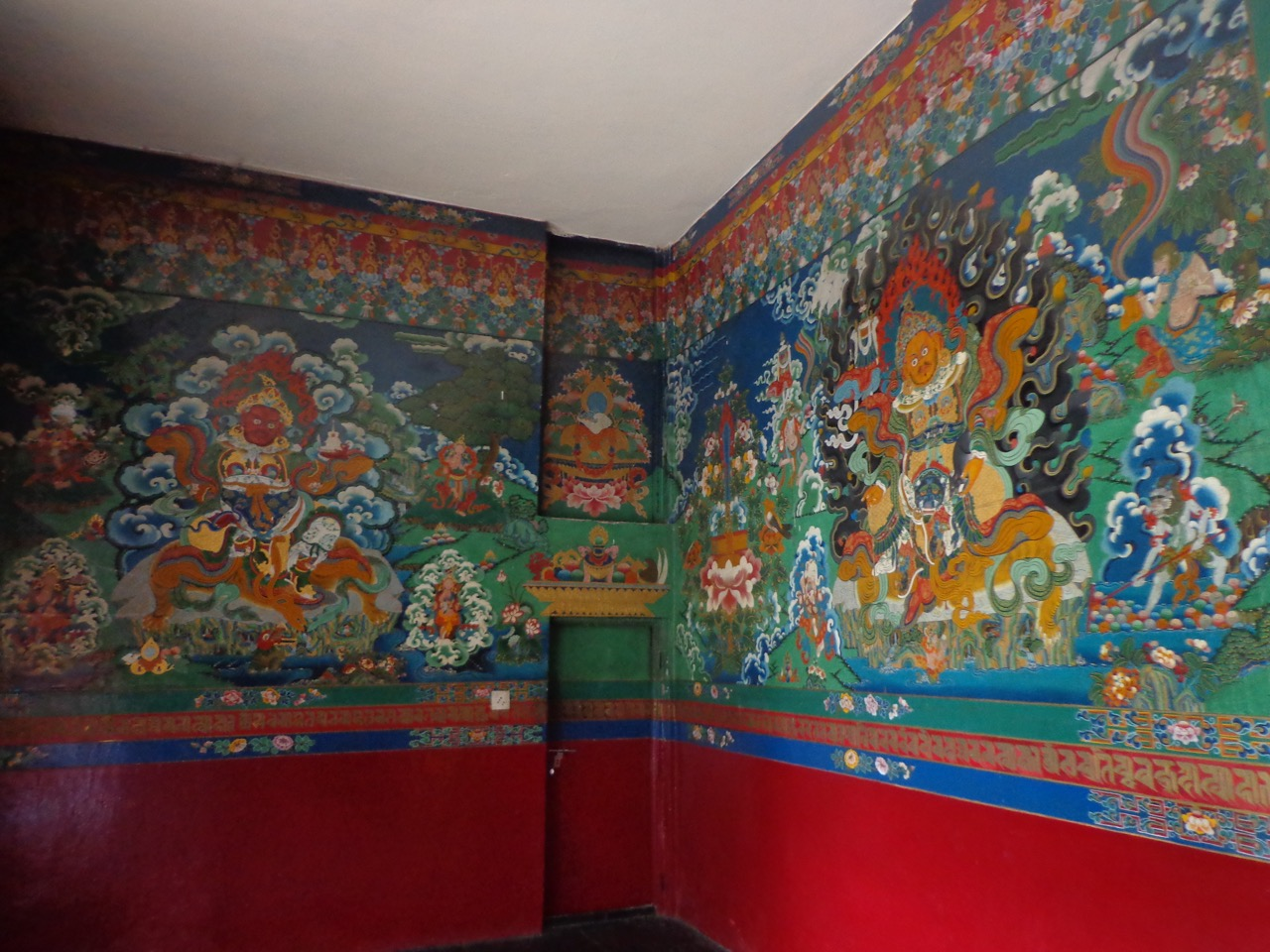 The walls are decorated with traditional Tibetan paintings.