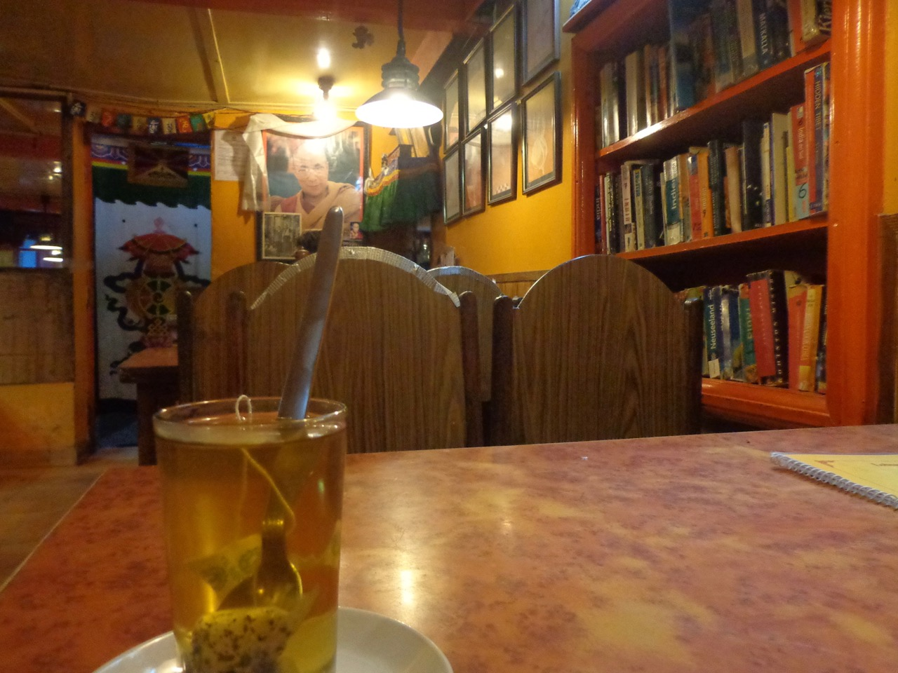 The bookshelf at Lobsang's Four Seasons Cafe overlooking the glass of Tibetan herbal tea.