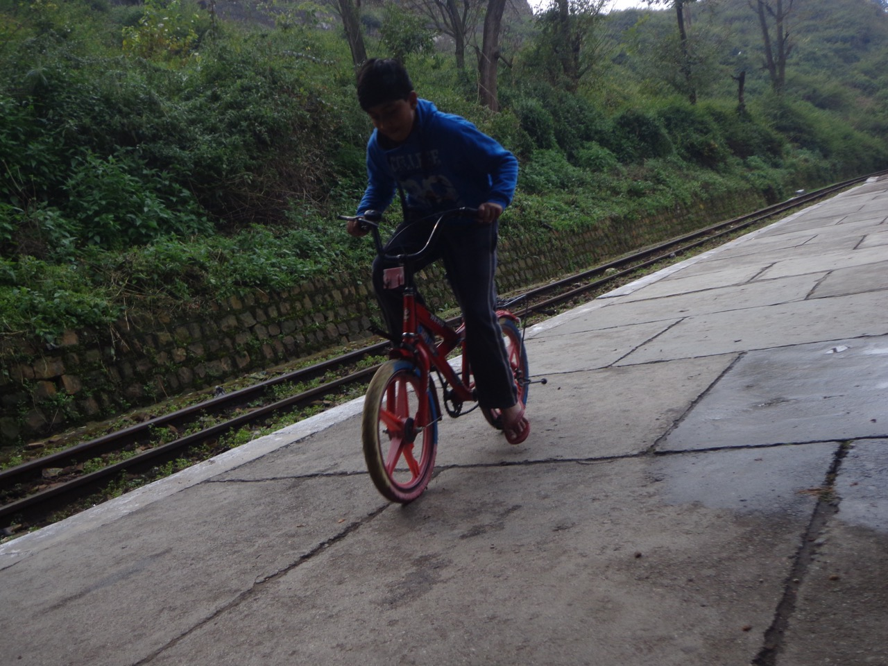 A kid was practicing his cycling skills on the small platform.