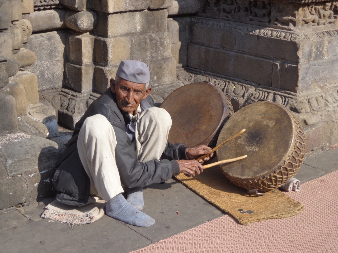 A drummer drums and begs inside the temple.