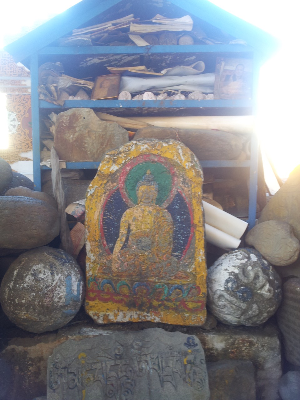 A Buddha idol painted on a stone slab.